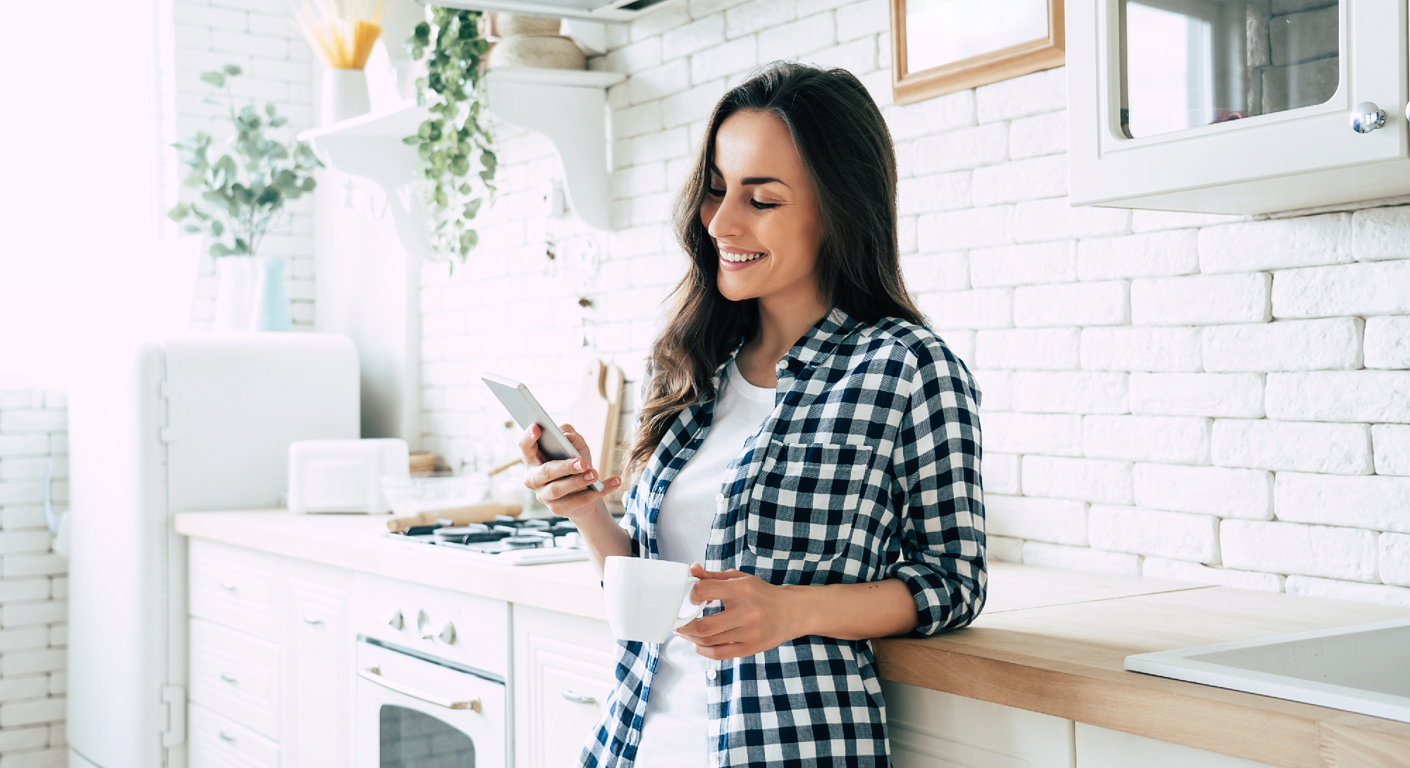 Woman holding coffee cup and looking at her phone in kitchen