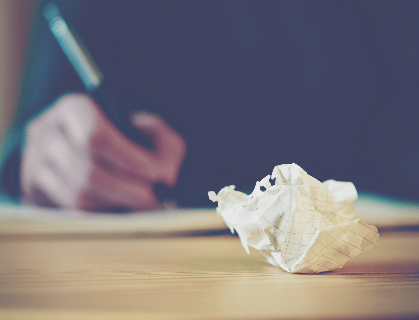person-writing-next-to-crumpled-paper