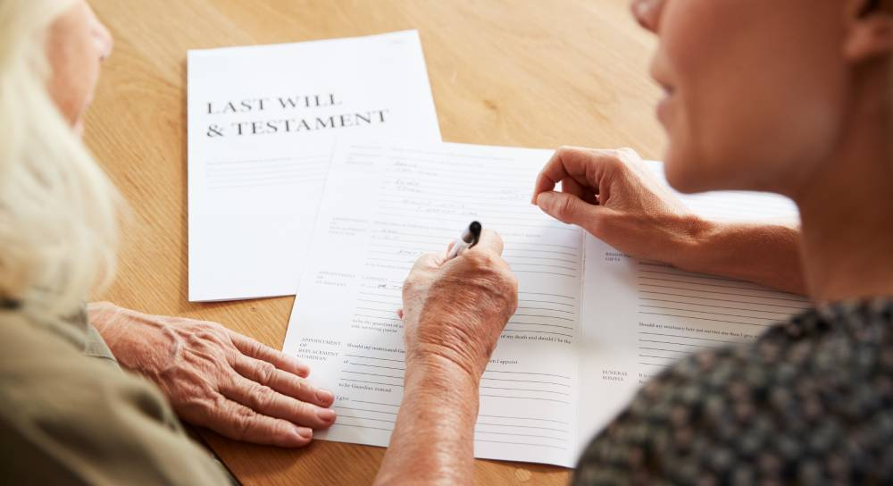 An elderly woman signs a Will with a younger woman present.
